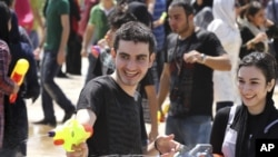 Young people shoot with water guns during a mass organized water fight in northern Tehran