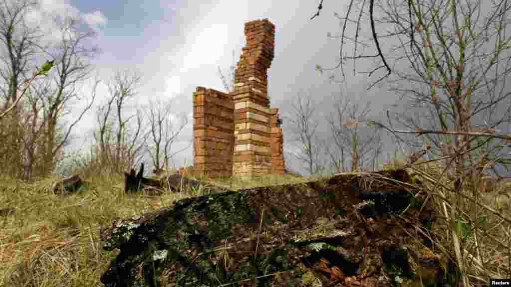 A brick chimney stands as the sole reminder of a house that was destroyed by fire in the abandoned village of Kazhushki, in the Chornobyl exclusion zone.