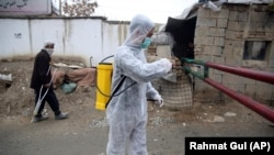 A volunteer in a protective suit sprays disinfectant outside a local police station to help curb the spread of coronavirus in the Afghan Kabul on March 23.