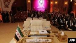 На саміті Ліги арабських держав на столі делегації Сирійської Арабської Республіки стоїть «прапор незалежності» 1930–50-х років, який використовує сирійська опозиція, 26 березня 2013 року