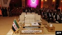 A pre-Ba'ath regime Syrian flag, currently used by the opposition, is seen in front of the seat of the Syrian delegation at the opening the Arab League summit in Doha on March 26.