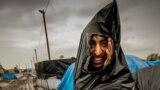Кале шаарындагы (Франция) &quot;Жаңы жунгли&quot; лагериндеги мигрант жаандан таштанды салынчу баштык менен коргонууда. 21-октябрь, 2015-жыл<br /> &nbsp;