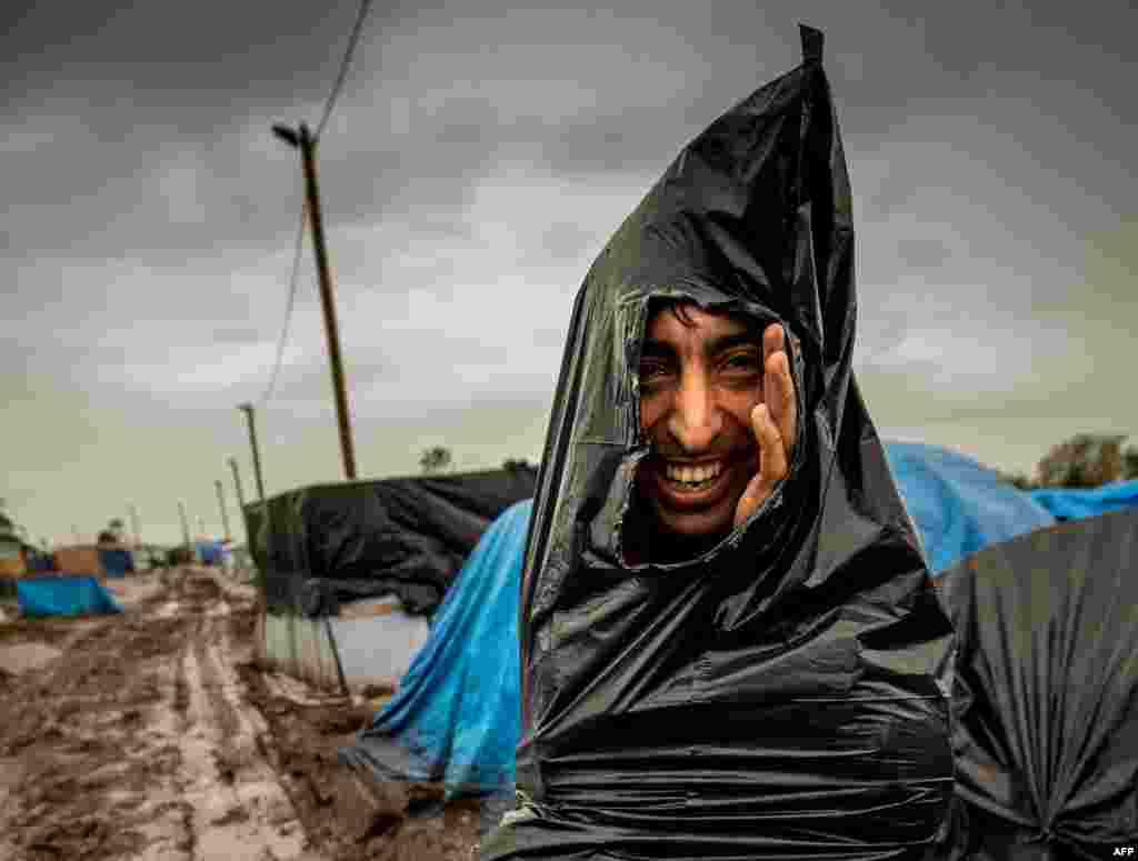 """Мигрант в лагере для беженцев """"Новые джунгли"""" в городе Кале (Франция) укрывается от дождя пластиковым мешком для мусора. 21 октября 2015 г."""