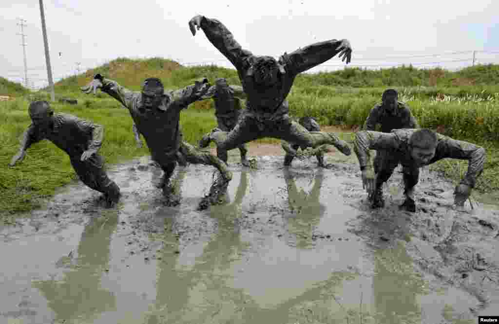Paramilitary policemen jump over muddy water during a training session at a military base in Chuzhou, Anhui Province, China. (Reuters/China Daily)