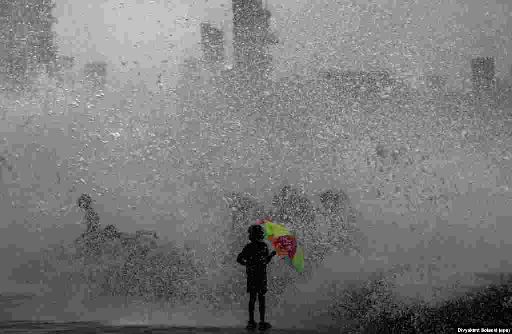 A youngsters holds a colorful umbrella while receiving a soaking after a high wave hit the shoreline during high tide in the Arabian Sea along the promenade in Mumbai, India. (epa/Divyakant Solanki)