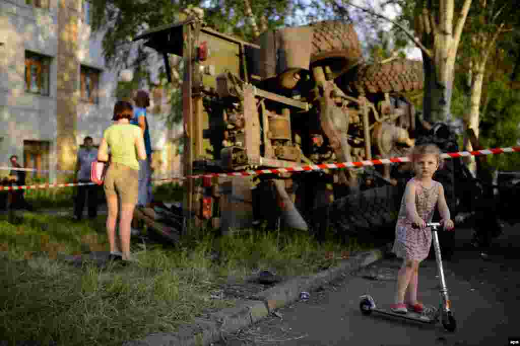 A girl plays in front of a destroyed truck, which was previously used by pro-Russian militants before being bombed by Ukrainian army soldiers, in Donetsk on May 27. (epa/Jakub Kaminski)
