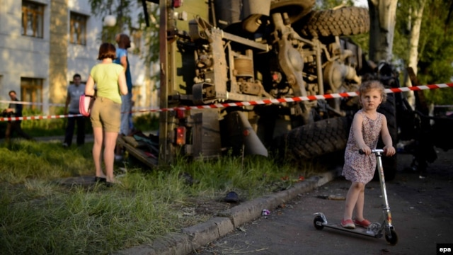 A girl plays  in front of a destroyed truck used by pro-Russian militants, which was bombed by Ukrainian Army soldiers during clashes in Donetsk on May 27.