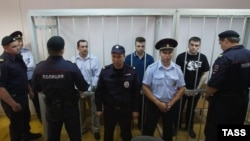 Russia -- Aleksander Margolin, Ilya Gushchin and Aleksei Gaskarov (L-R), charged with rioting on Bolotnaya Square on May 6, 2012, are seen in a cage during the announcement of the verdict in a Moscw court, Aug. 18, 2014
