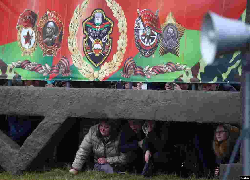 Kasam kabul edýän belarus esgerlerini synlaýan adamlar. Borisow şäheriniň golaýyndaky baza. (Reuters/Vasily Fedosenko)