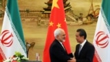Iranian Foreign Minister Mohammad Javad Zarif (left) shakes hands with his Chinese counterpart, Wang Yi, at a bilateral meeting in Beijing. Iran has in recent months increasingly reached out to China in the face of growing U.S. pressure to isolate Tehran. (file photo)