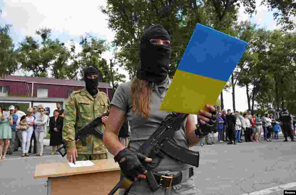 "A female member of the ""Donbas"" self-defence battalion swears an oath to be officially included into the reserve battalion of the National Guard of Ukraine near Kyiv on June 23. (Reuters/Valentyn Ogirenko)"