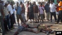 Жители сомалийского города Могадишо стоят возле тел двух погибших горожан. Иллюстративное фото.