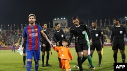 FILE: FC Barcelona Lionel Messi (L) holds the hands of Afghan boy Murtaza Ahmadi on the pitch before the start of a friendly football match against Saudi Arabia's Al-Ahli FC in Doha (December 2016).