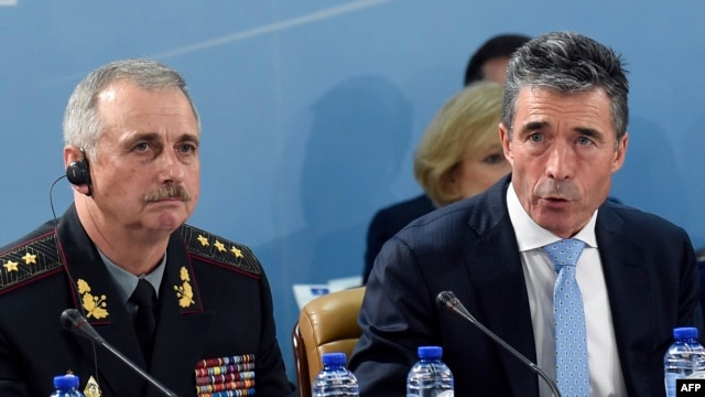 NATO Secretary-General Anders Fogh Rasmussen (right), flanked by acting Ukrainian Defense Minister Mykhaylo Koval, speaks during a defense ministers' meeting at NATO headquarters in Brussels on June 3.