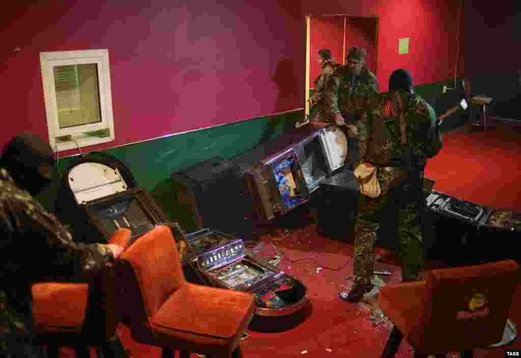 Pro-Russia militia men destroy gambling machines in one of the gaming clubs in Slovyansk, Ukraine, on May 12. (ITAR-TASS/Mikhail Pochuyev)