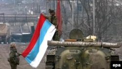 Russian soldiers unfold their flag in Grozny in 2000