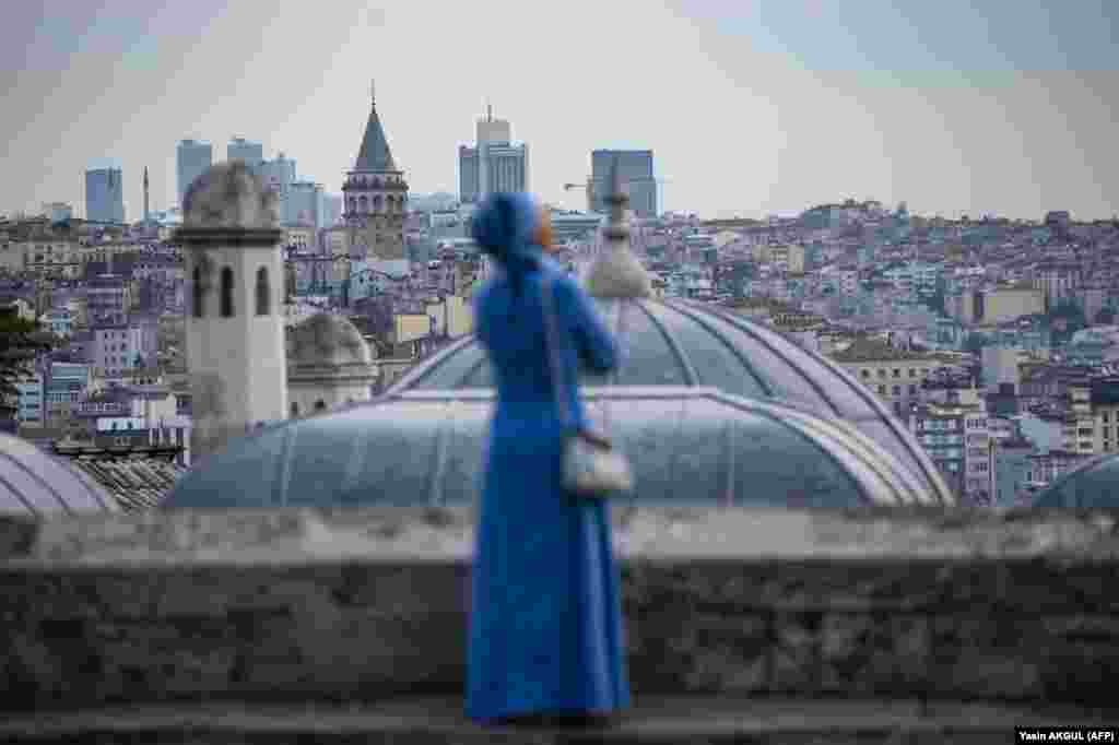 A woman looks out from the terrace of the Suleymaniye mosque after Eid al-Fitr prayers in Istanbul, Turkey. (AFP/Yasin Akgul)