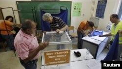 Сайлау комиссиясы өкілдері дауыс беру жәшігін орнатып жатыр. Афина, 15 маусым 2012 жыл.