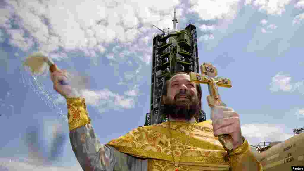 An Orthodox priest conducts a service in front of the Soyuz TMA-04M spacecraft set on its launch pad at Kazakhstan's Baikonur Cosmodrome. (Reuters/Shamil Zhumatov)