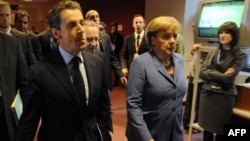 German Chancellor Angela Merkel (second from right) and French President Nicolas Sarkozy (second from left) on their way to brief the press on the outcome of eurozone debt talks.