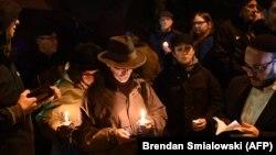 Люди со свечами у входа в синагогу Питтсбурга, где произошла стрельба
