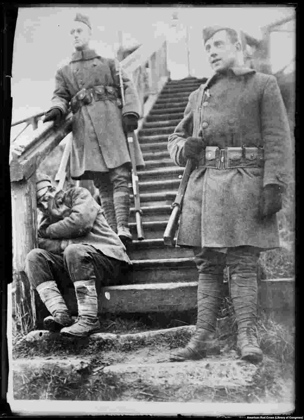 """""""შიმშილით დასუსტებული"""" რუსი გლეხი არხანგელსკში აშშ-ის შტაბბინის კიბეზე 1918 ან 1919 წელს. რუსეთში ძალაუფლების ბოლშევიკების ხელში გადასვლას ამერიკელების მხრიდან ჯერ """"მოლოდინისა და დაკვირვების"""" პერიოდი მოჰყვა, თუმცა ურთიერთობა მალე გაფუჭდა და აშშ-ის ჯარები მხარში ამოუდგნენ ბრიტანელებსა და სხვა მოკავშირეებს თეთრგვარდიელების დასახმარებლად."""