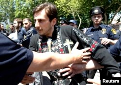 Georgian police try to stop an Orthodox Christian activist during clashes at a rally to mark International Day Against Homophobia in Tbilisi on May 17.