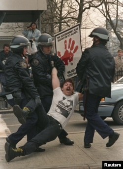New York police arrest one of several dozen demonstrators who blocked streets by city hall to protest Mayor Ed Koch's AIDS policies on March 28, 1989.