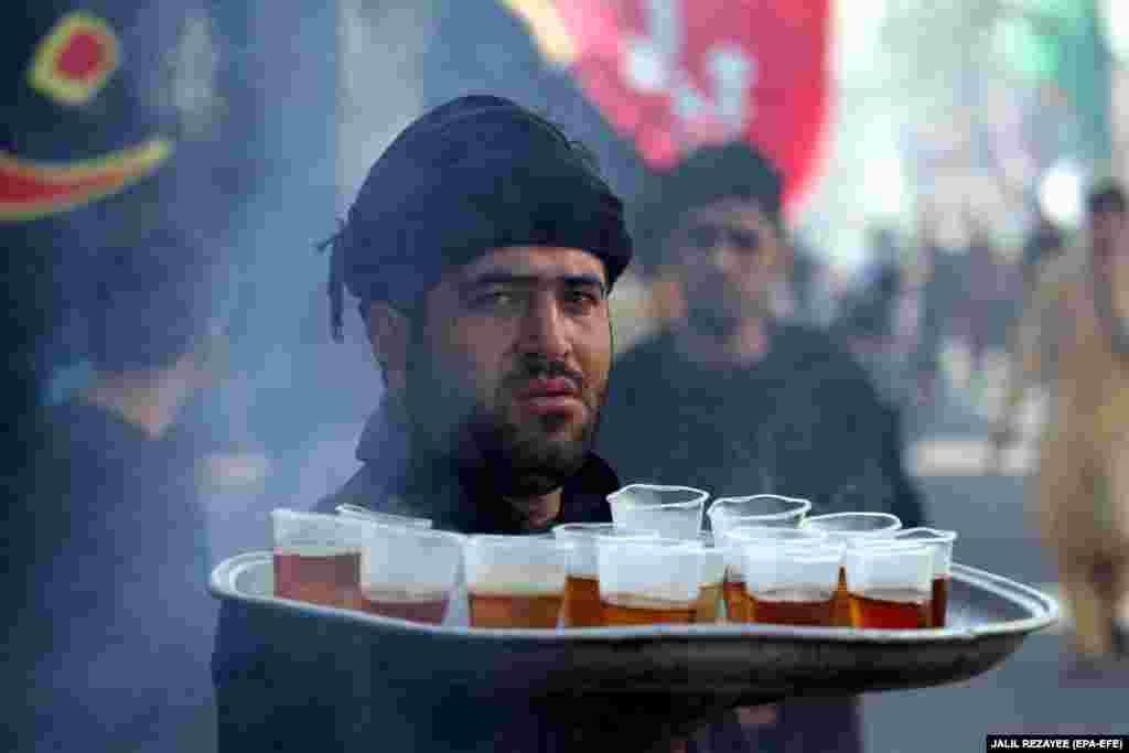 An Afghan Shi'ite Muslim serves drinks during the Islamic sacred month of Muharram in Herat, Afghanistan. (epa-EFE/Jalil Rezayee)