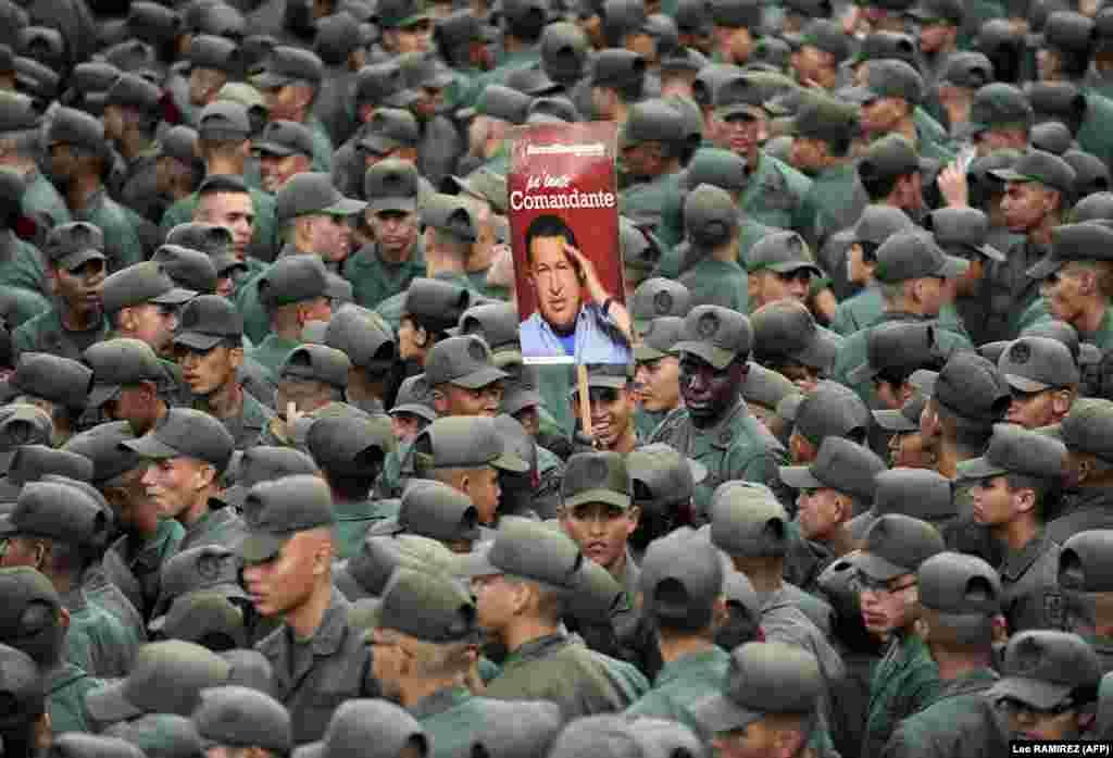 Venezuelan soldiers hold a poster of President Hugo Chavez during a commemoration in Caracas of the failed 1992 coup led by Chavez, who was an army lieutenant colonel, against then-President Carlos Andres Perez. (AFP/Leo Ramirez)