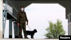 Grănicer mascat, pentru a se proteja de contaminare, la frontiera Kazahstanului cu China.