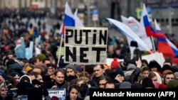 "A protester holds a placard reading ""Putin - No!"" during an opposition rally in central Moscow in March 2019 to demand Internet freedom in Russia."