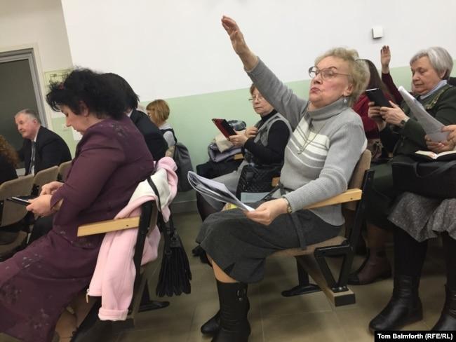Os membros da congregação levantam as mãos durante o serviço esperando que eles sejam selecionados para ler em voz alta.