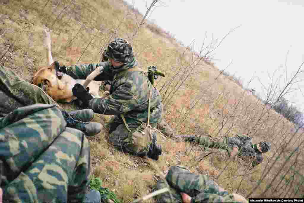 One soldier plays with a dog named Kalashnikov while others fall asleep on the grass during a short break.