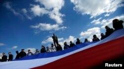Ленин ескерткіші алдында Қырым туын ұстап тұрған адамдар. Симферополь, 18 наурыз 2014 жыл. (Көрнекі сурет)