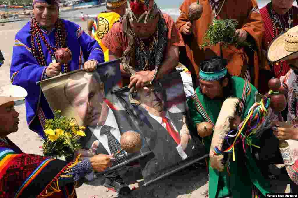 Перуанские шаманы с плакатами, изображающими президента России Владимира Путина и президента США Дональда Трампа, проводят ритуал предсказаний на следующий год. Пляж Пескадорес, Чорийос, Лима, 27 декабря 2018 года.