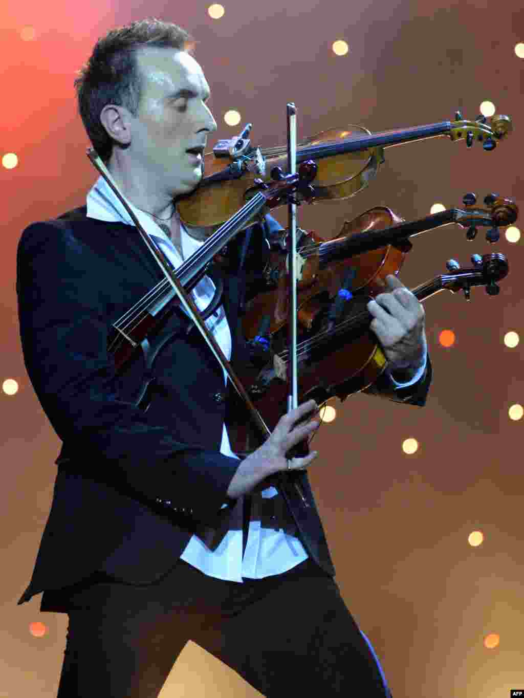 """Ukrainian virtuoso Oleksandr Bozhyk plays four violins at the same time as he performs ''Requiem For A Dream"""" by Clint Mansell during a solo concert in the western Ukrainian city of Lviv. (AFP/Yuriy Dyachyshyn)"""