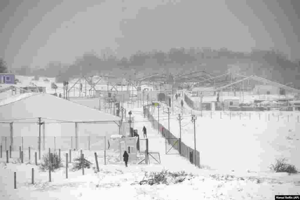 Refugiați mergând prin zăpada care s-a așternut deja peste tabăra arsă de la Lipa, pe 26 decembrie. Tabăra provizorie de corturi de la Lipa a fost deschisă pe 21 aprilie și era destinată doar bărbaților. Potrivit Organizației Internaționale pentru Migrație (OIM), această tabără a găzduit 1359 de migranți.