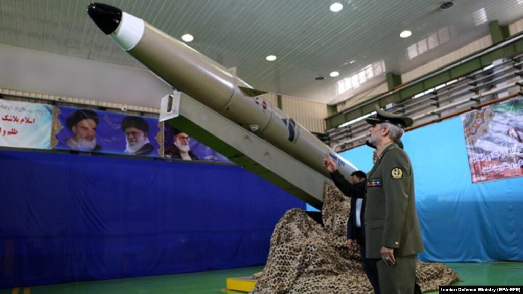 Iranian Defense Minister Amir Hatami stands next to a new Fateh-e Mobin short-range ballistic missile.