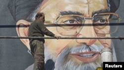 Ready for a makeover? An worker rests in front of a huge portrait of Supreme Leader Ayatollah Ali Khamenei on a wall near a Tehran university in late February.