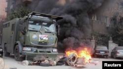 Египеттің бұрынғы президенті Мұхаммед Мурсиді қолдаушылар мен қауіпсіздік күштері арасындағы қақтығыс кезінде өртенген полиция көлігі. Каир, 31 қаңтар 2014 жыл.