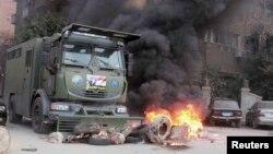 Підпалене поліцейське авто - наслідок сутички прихильників і супротивників Мурсі, 2014 рік