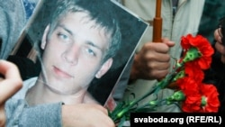 A mourner in Minsk holds a photograph of Ihar Ptsichkin, who died in prison under mysterious circumstances.