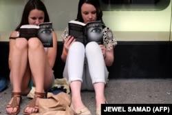 دو خواننده رمان «پنجاه طیف...» در انتظار برای دریافت امضای نویسنده، در نیویورک، ۲۰۱۵