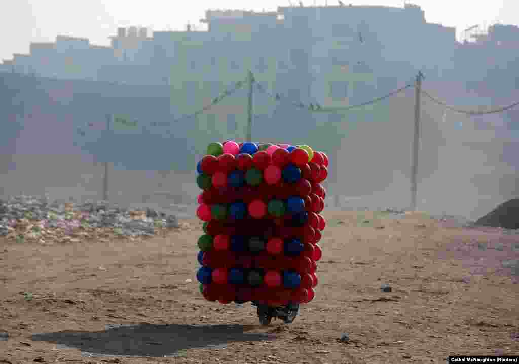 A man carries children's colored plastic balls on his motorcycle in Delhi. (Reuters/Cathal McNaughton)