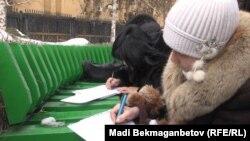 Ұлттық банк алдында арыз жазып отырған борышкерлер. Алматы, 19 ақпан 2014 жыл. (Көрнекі сурет)
