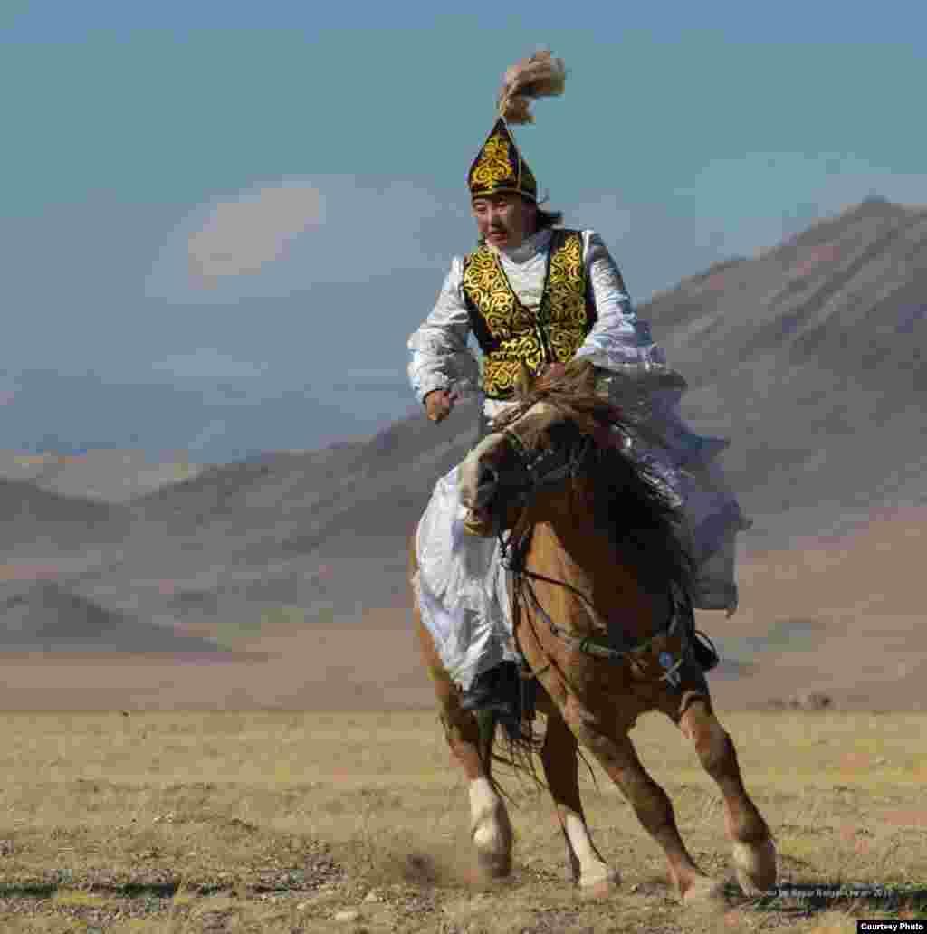 Молодая женщина скачет на коне во время праздничного состязания.
