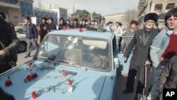 Жители Баку возле обстрелянной машины.