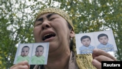 An ethnic Uzbek refugee shows photos of her missing grandsons as she stands on the Kyrgyz-Uzbek border on June 15.