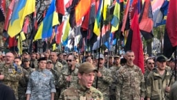 Thousands of Ukrainians march through Kyiv under flags and banners of right-wing and nationalist groups on October 14 as part of ceremonies marking the Defenders Day holiday.
